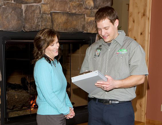 Alpine Cleaning & Restoration team member next to lady in front of fire place - representing Exceptional Customer Service